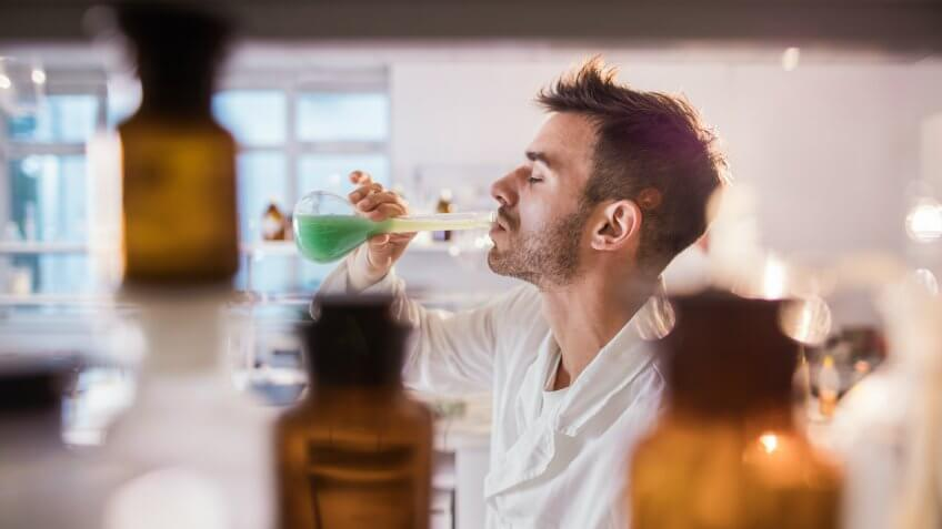 Young scientist drinking toxic substance from a beaker in laboratory.
