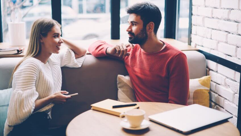 Young woman and man talking during first date in cozy coffee shop enjoying free time together,hipster girl checking notification on mobile while spending time with boyfriend having lovely conversation - Image.