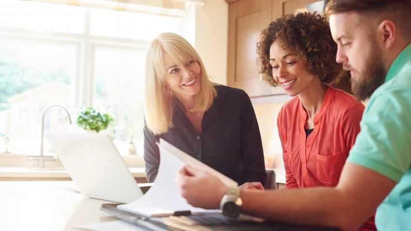 a couple sit in the kitchen of a show home and discuss some figures with the estate agent or mortgage advisor.