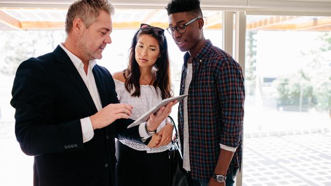 Realtor showing terms of contract on tablet to interracial couple.