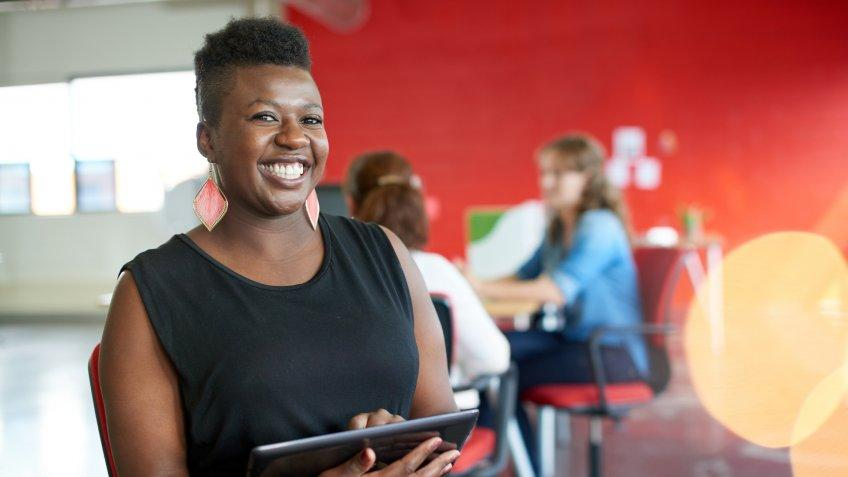 Casual portrait of an african american business woman using technology in a bright and sunny startup with the team in the background.