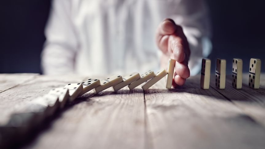 Stopping the domino effect concept for business solution, strategy and successful intervention.