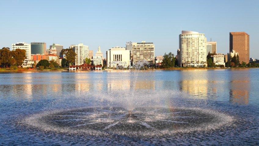 Downtown Oakland skyline along the banks of Lake Merritt .