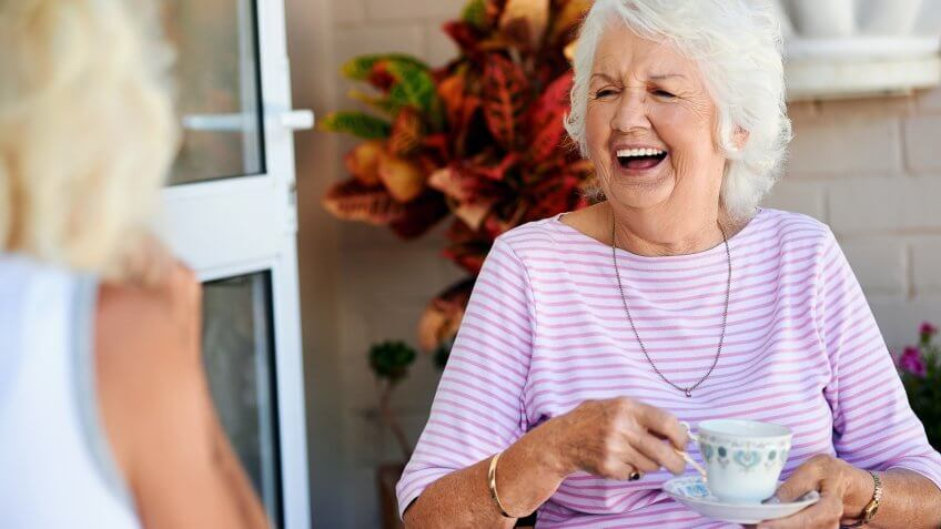 elderly woman laughing with her lady friend