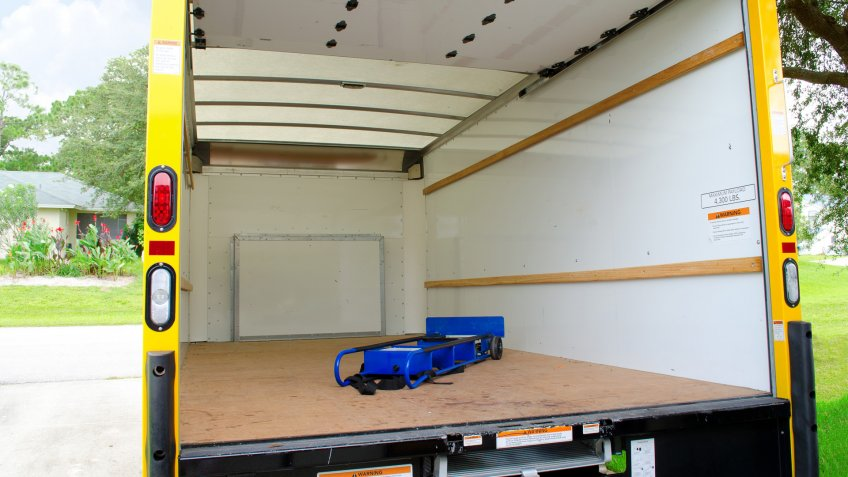 Empty yellow moving truck with blue dolly in back.