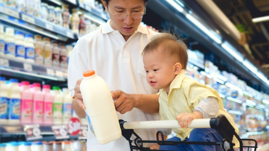 father and baby son looking at milk jug