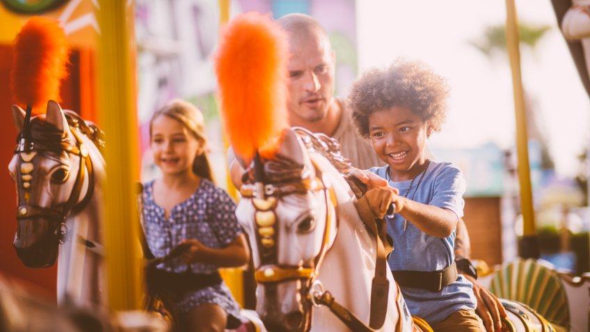 Multi-ethnic family boy having fun with father riding horse on merry-go-round amusement park ride.