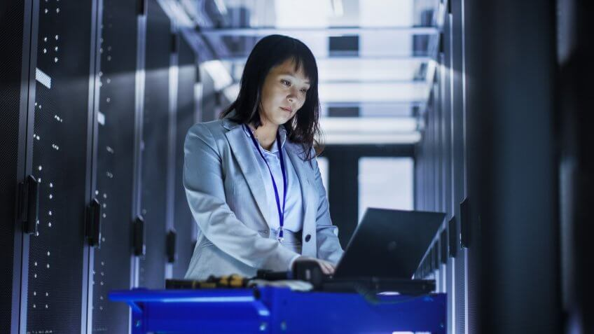 Asian Female IT Engineer Working on a Laptop on Tool Cart, She Scans Hard Drives.