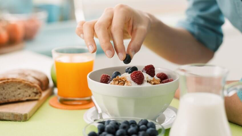 Woman having an healthy delicious breakfast at home with yogurt, cereals and fresh fruit, she is picking a blueberry.
