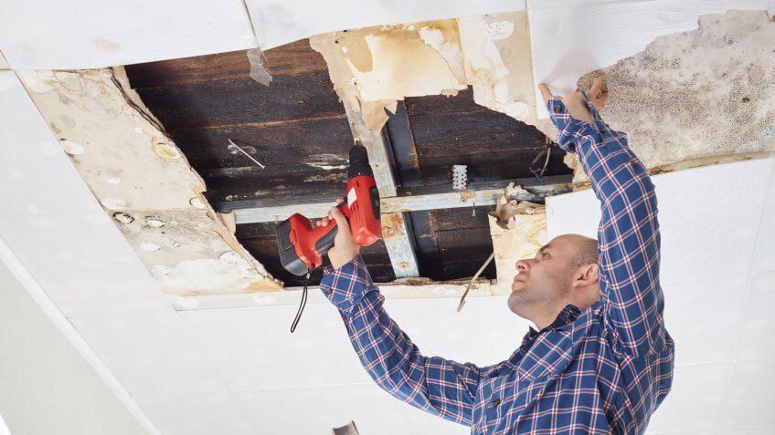 Man repairing collapsed ceiling.