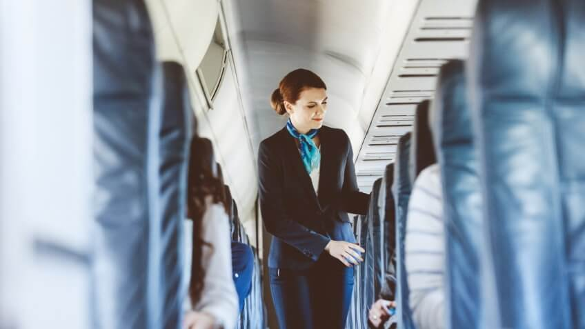 flight attendant standing in the aisle of an airplane