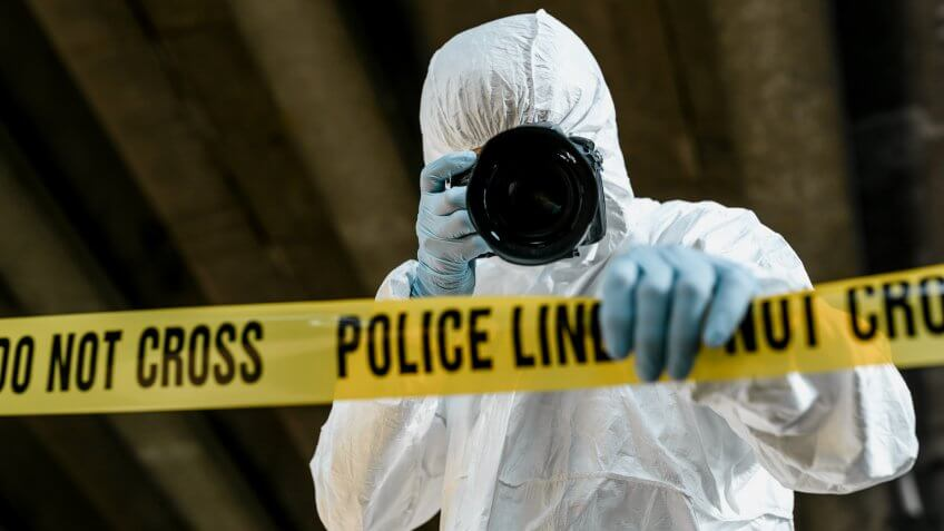 forensic science technician photographing the scene of a crime