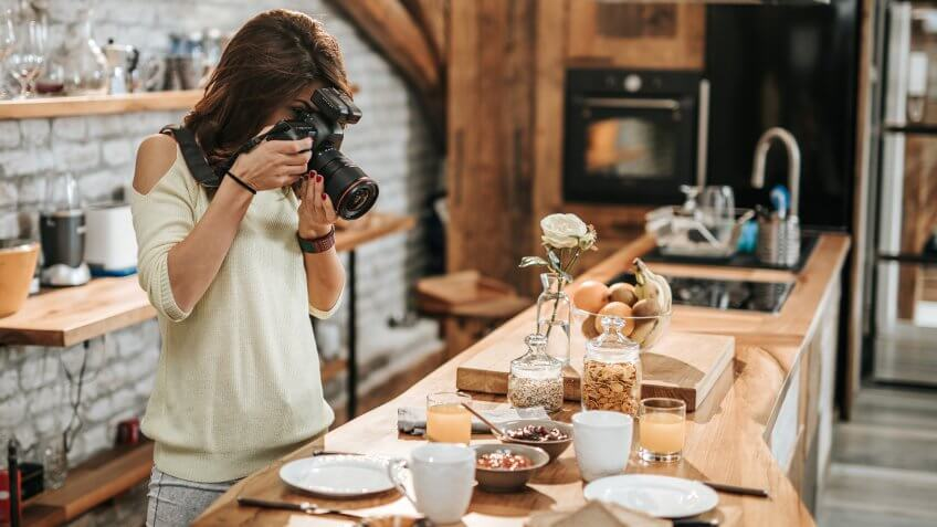 Young female photographer taking photos of breakfast table in the kitchen.