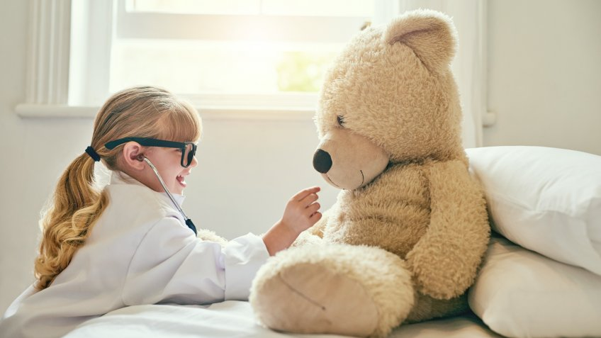 girl holding stethoscope against big teddy bear