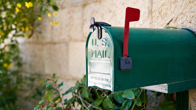 Green US post mail letter box with red flag raised up.