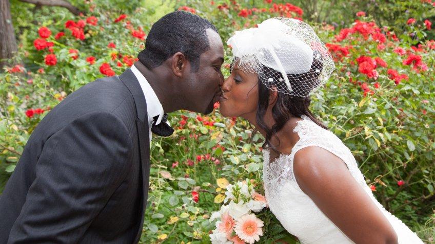 groom and bride kissing in garden