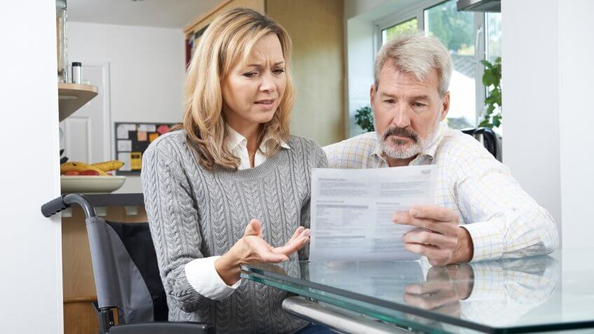 handicapped woman reviewing finances with her husband at home