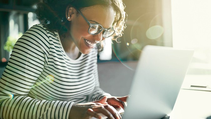 Young African woman wearing glasses smiling while sitting alone at a table working online with a laptop.