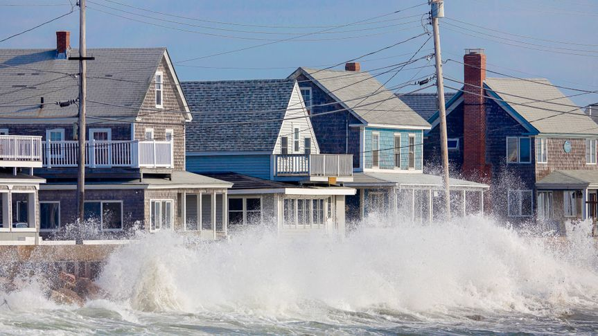 Waves crash against a break wall in conjunction with high tide and a storm.