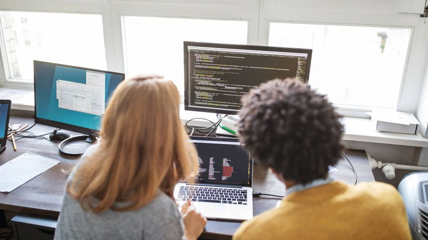 Rear view of male and female computer programmers working on a new project together in office.