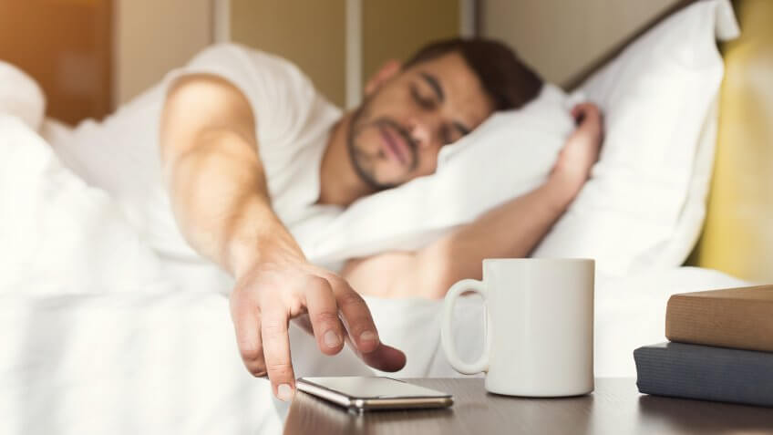 Sleepy guy waking up early after hearing alarm clock signal on smartphone on monday morning, reaching for ringing mobile phone with closed eyes, copy space.