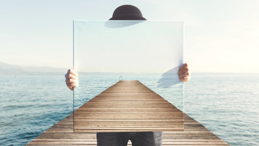 Man holding surreal painting of a boardwalk.