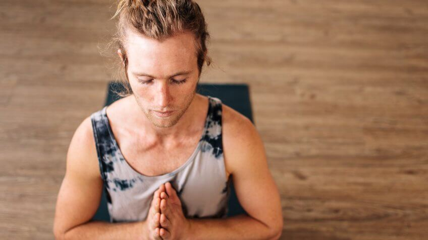 Over head view of fit young man practice yoga sitting on floor with his hands joined.