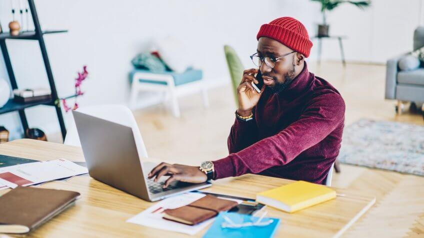 man on phone while using laptop