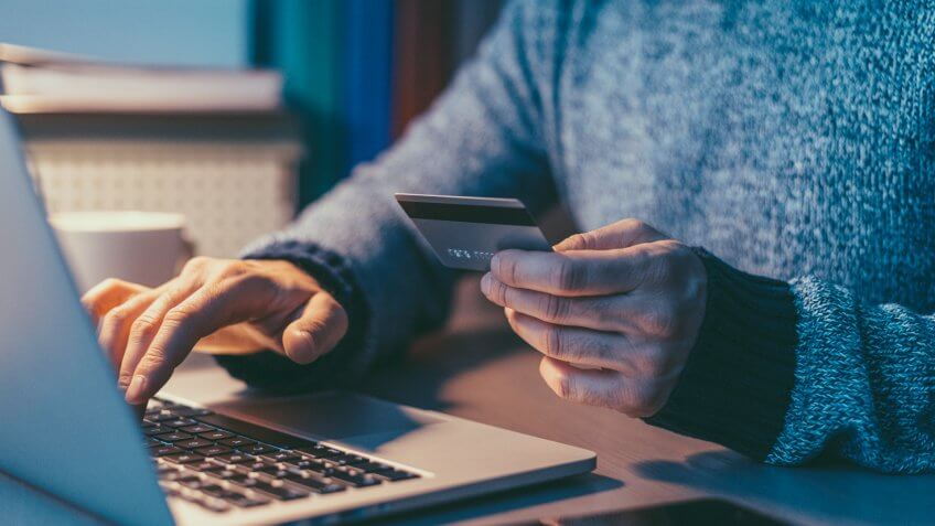 man with credit card in front of laptop