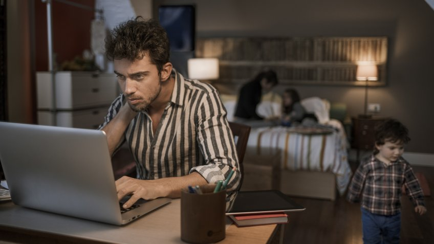 Man working late with laptop with family in the background.