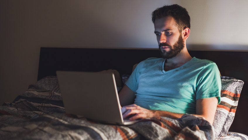 Young man working late in bed on a laptop.