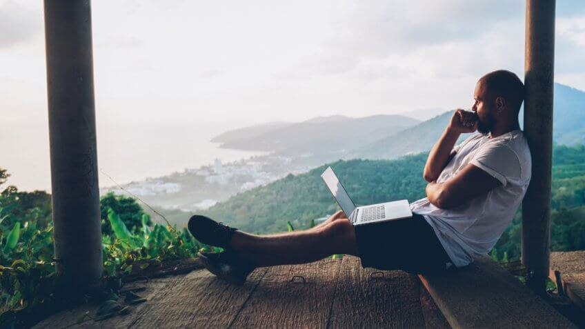 Thoughtful young man looking away on beautiful nature landscape while sitting with laptop computer outdoors.