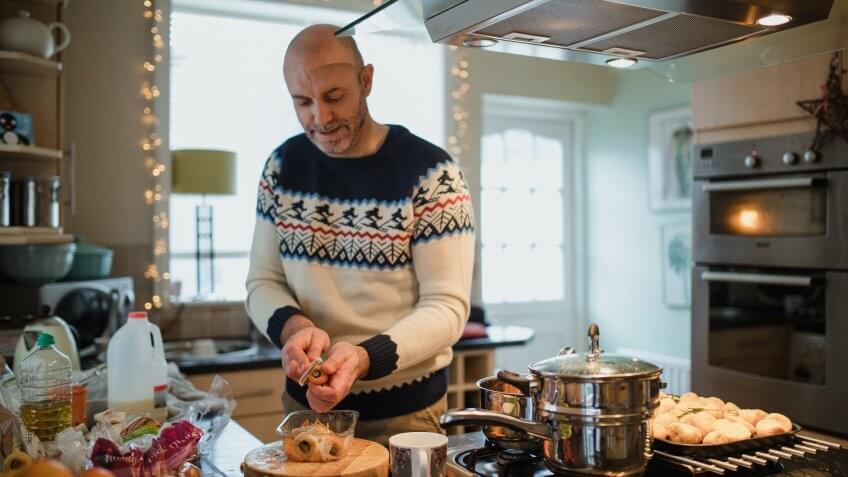 One mature man is preparing a christmas dinner in the kitchen of his home.