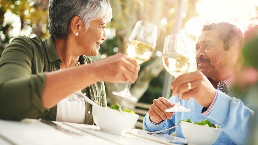Shot of a happy older couple sharing a toast over lunch outdoors.