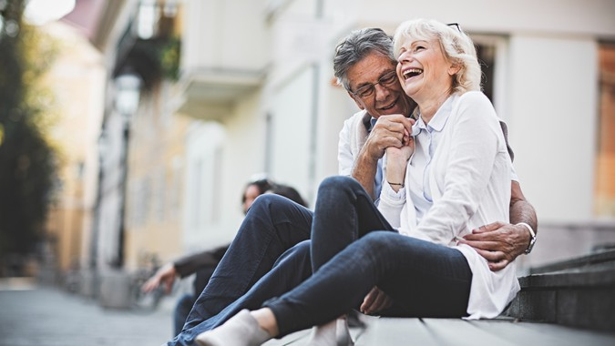 Happy senior couple sitting on a bench in city center.