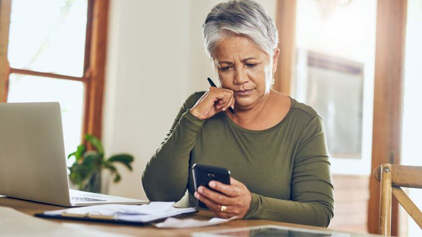 mature woman using a cellphone while going through paperwork at home.