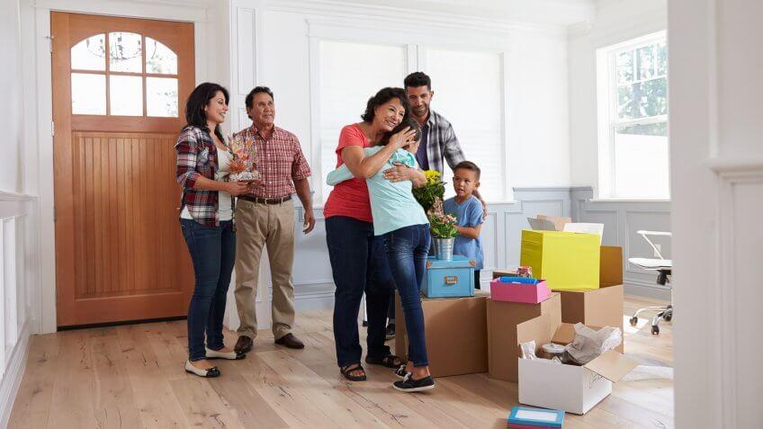 Grandparents Visiting Hispanic Family In New Home.
