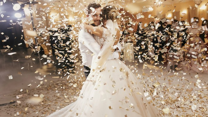 Gorgeous bride and stylish groom dancing under golden confetti at wedding reception.
