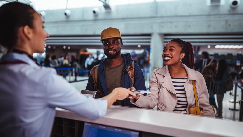 Young African-American couple doing check-in at airline check-in counter at international airport.