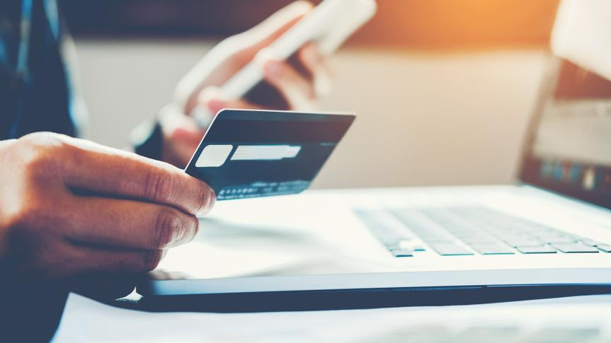 Man Holding Credit Card And Using Cell Phone holding credit card with shopping online.
