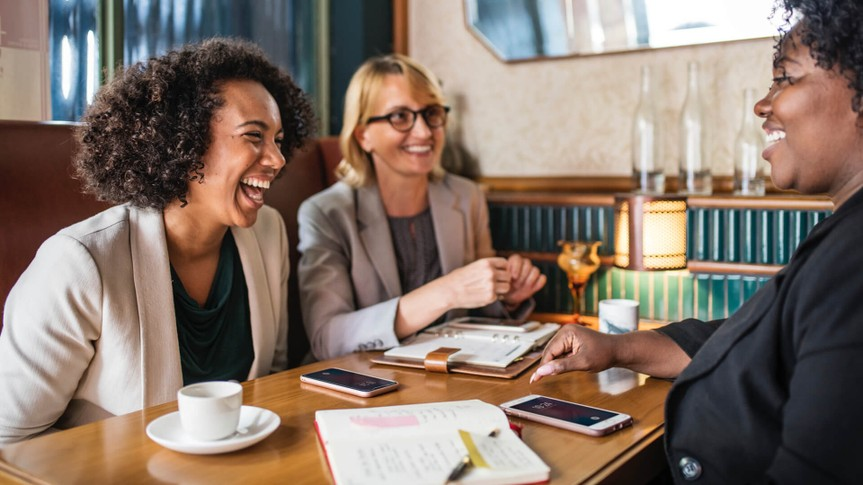professional women laughing in a meeting
