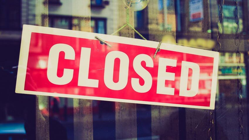 red closed store sign on door