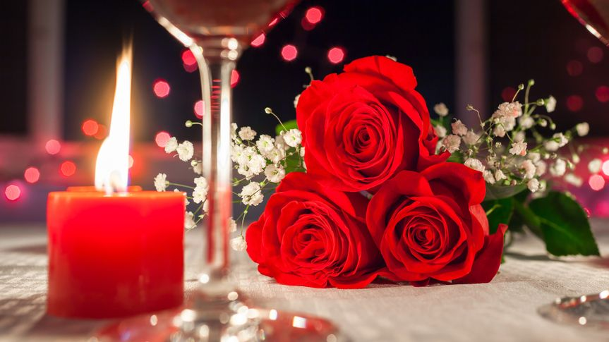 Red roses and candlelight romantic dinner setting.