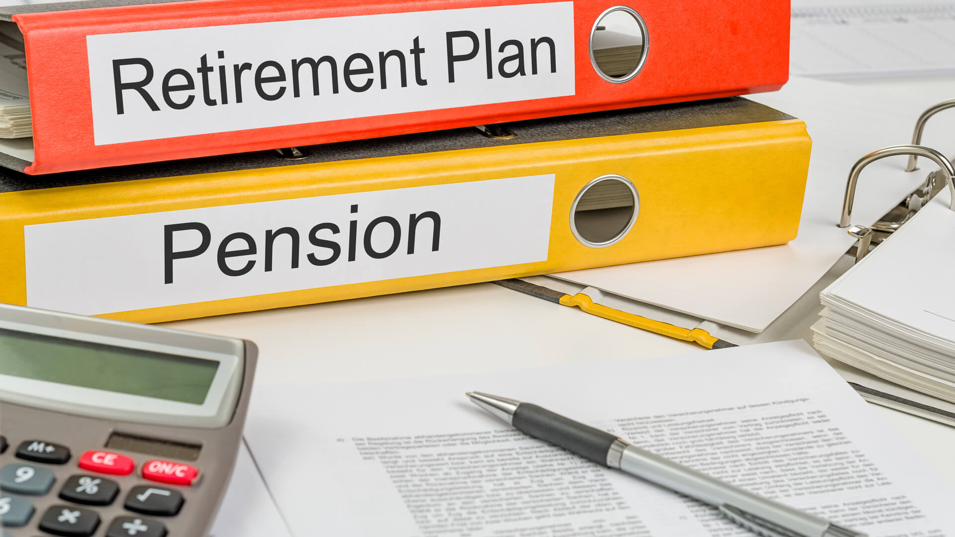 retirement plan and pension plan folders on desk