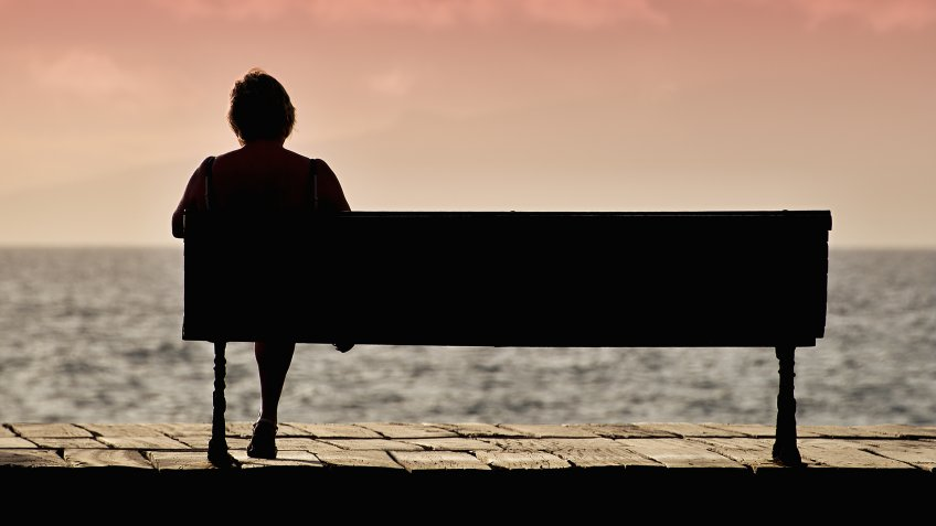 Silhouette of senior woman sitting alone on the bench in front of the sea - Image.