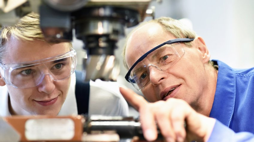 closeup picture: trainer and apprentice in vocational training on a milling machine - teacher explains details of the machine.