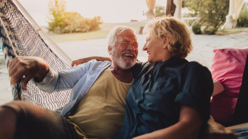 Photo of a senior couple having a relaxing moment in a hammock on a terrace of their family home by the sea.