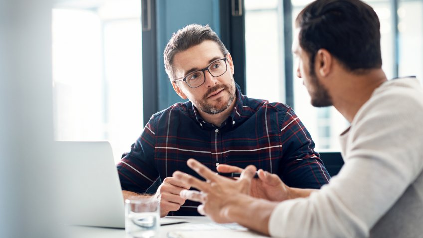 Shot of two businessmen having a discussion in an office.