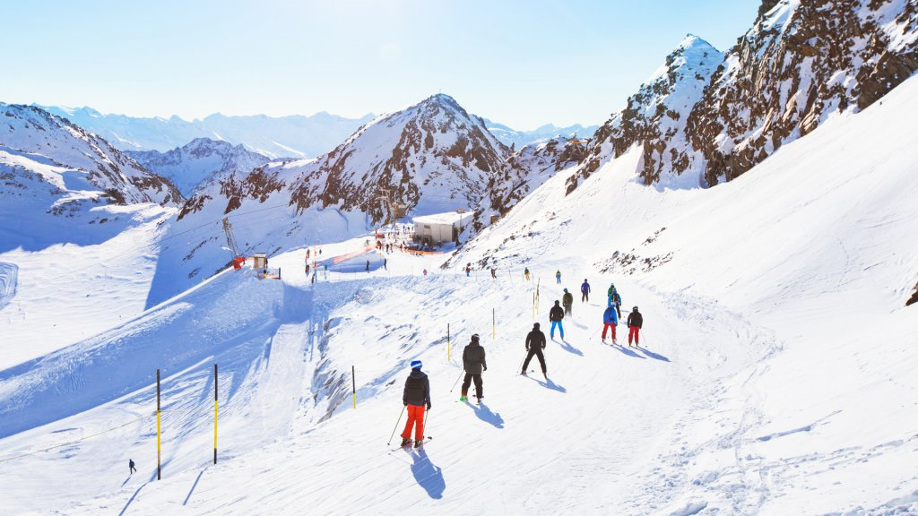 skiers on beautiful ski slope in Alps, people on winter holidays.