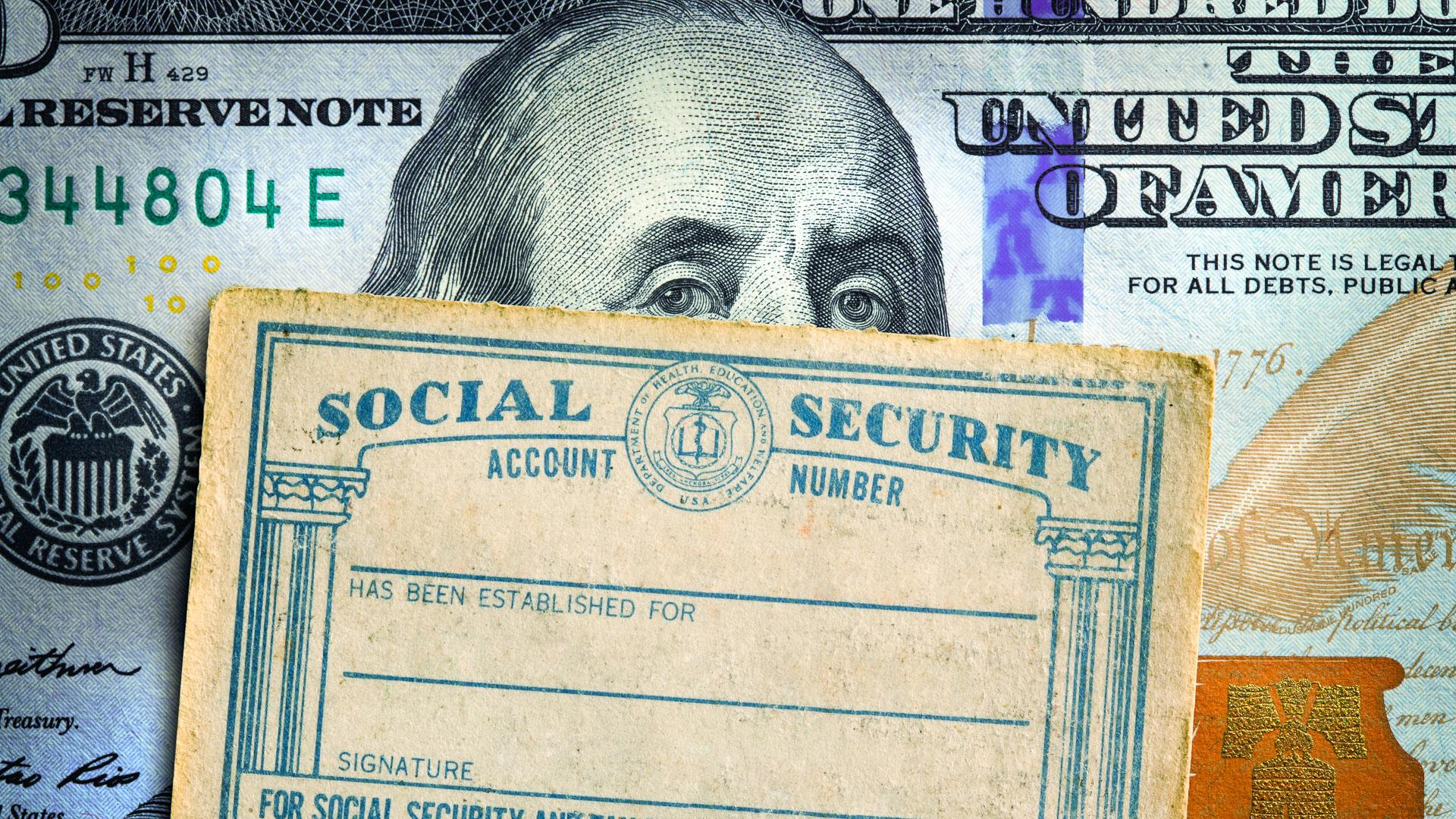A Social Security card rests on top of a one hundred dollar bill.